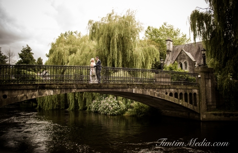 Bride and Groom embrace on a bridge in UCC Cork on their wedding day